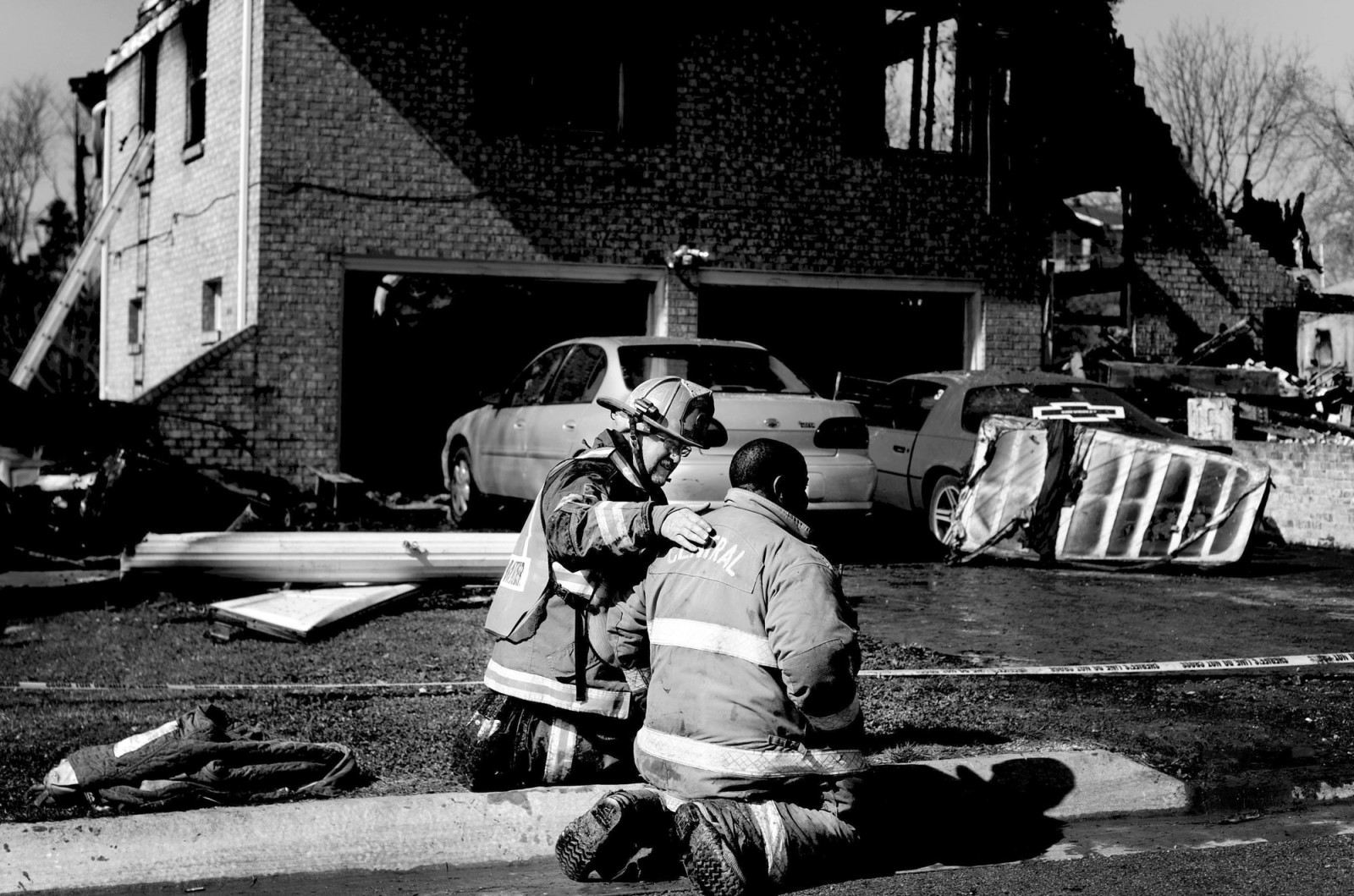 Gary Berendzen consoles Justin Barksdale after the body of a 6-year-old was finally recovered from the home that was destroyed by fire overnight in Holt's Summit, Mo. The fire started around 3:00 am and claimed the lives of three children..