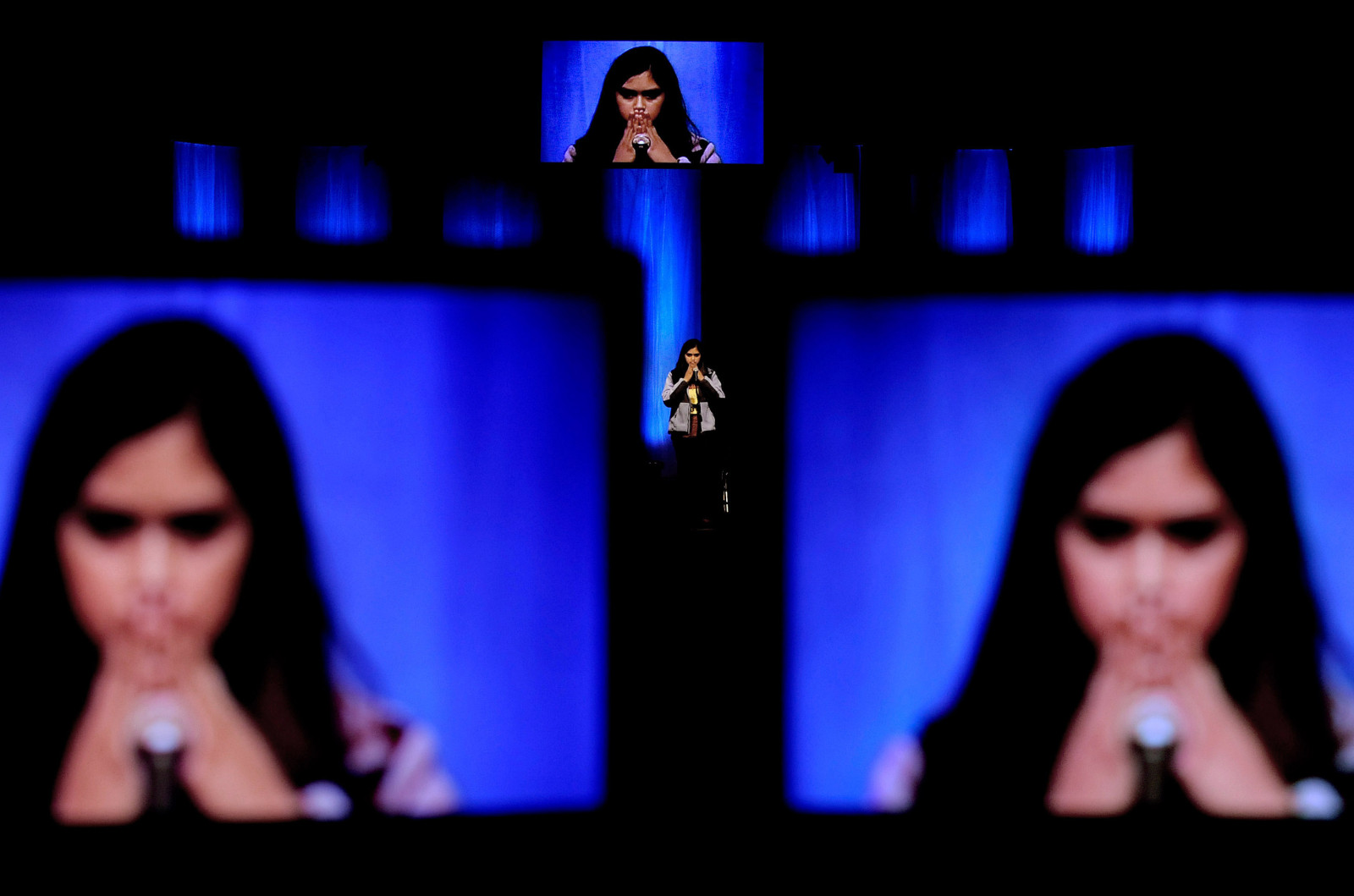 Contestant Afsah Khan is shown on television monitors as she thinks about her word during the Regional Spelling Bee at Christian Fellowship Church in Columbia, Mo. Khan placed third in the competition..