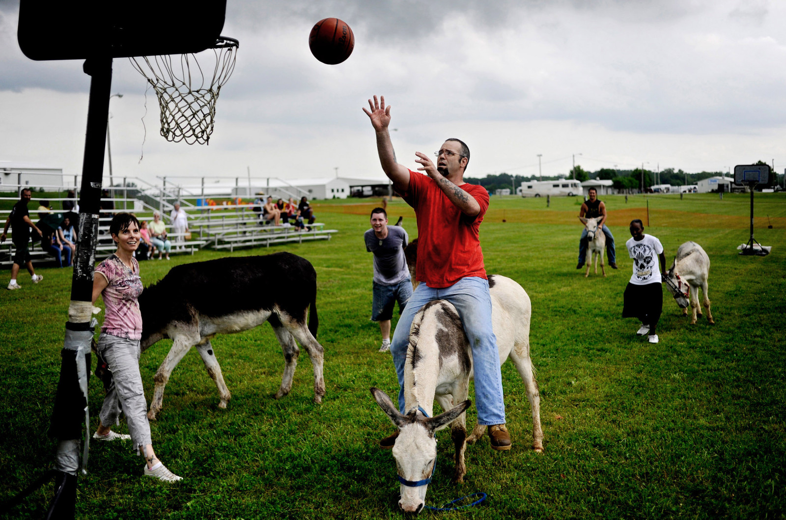 City councilwoman Laura Nauser, left, watches teammate Eddie Murray make a basket during a donkey basketball game. The fundraising event at the Boone County Fairgrounds benefitting the  Columbia-based youth literacy and education organization Destiny of H.O.P.E.