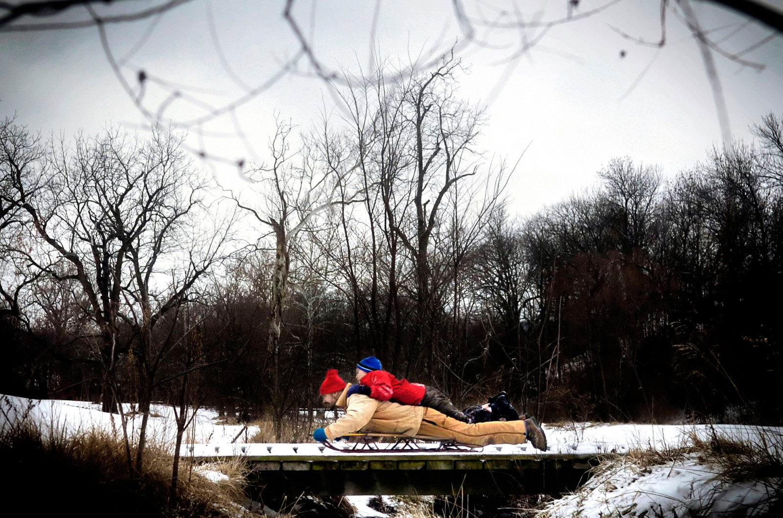 Brent Hagar and his 8 year-old son Levi slide across an ice-covered bridge at Stephens Lake Park in Columbia, Mo. after sledding down a nearby hill during a mid-January snow day..
