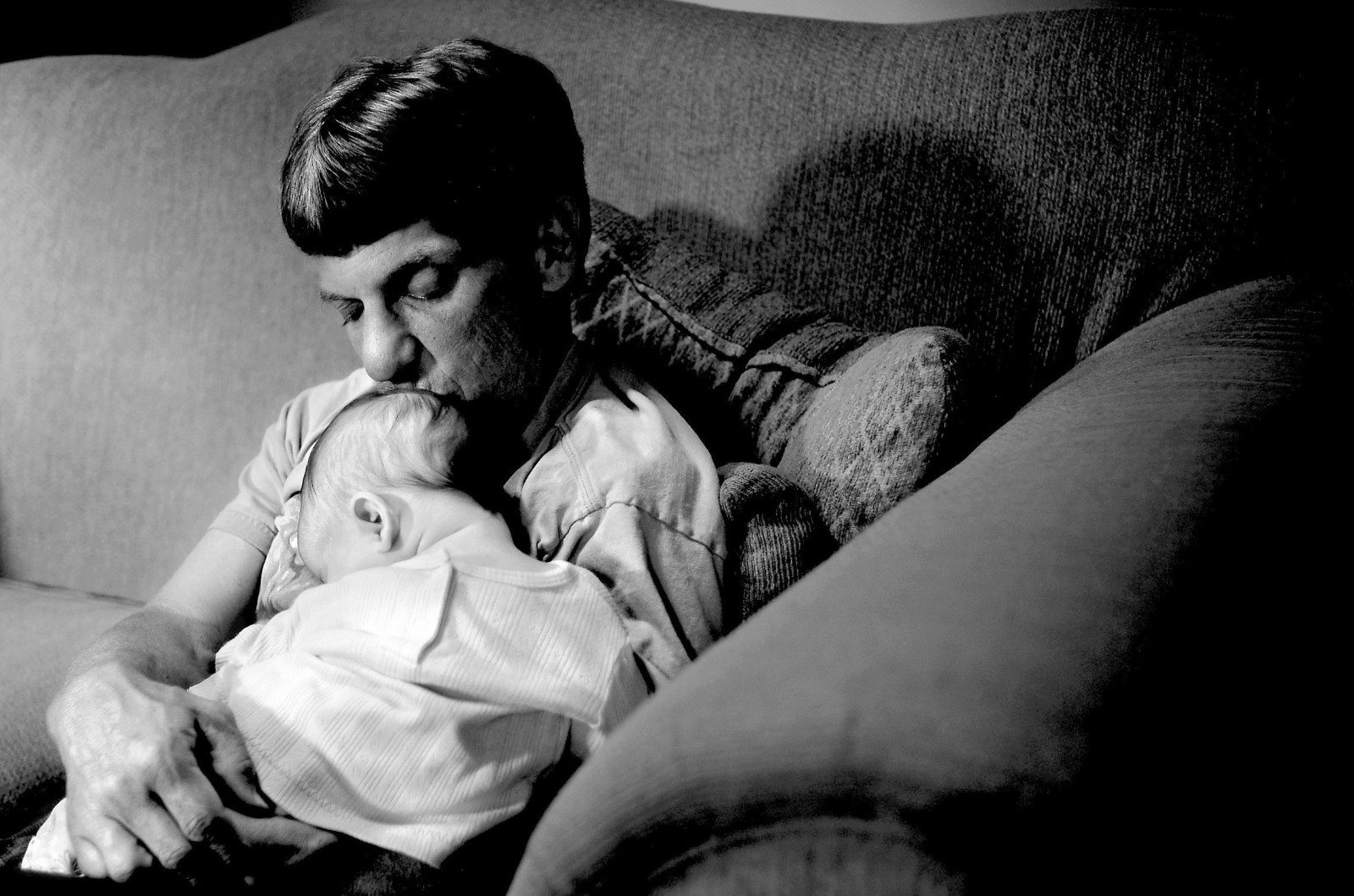 """Mark McGimsey kisses his 3-month-old daughter, Maeghan, on the family's living room. At 4 feet 8¬Ohm inches tall, McGimsey is a dwarf, and the condition has caused him significant medical problems. """"The disability has allowed me to be a stay-at-home dad,"""" he said. """"I had a great job, but it pales in comparison to being able to stay home with my children. There's nothing better than a sleeping baby on your chest."""""""