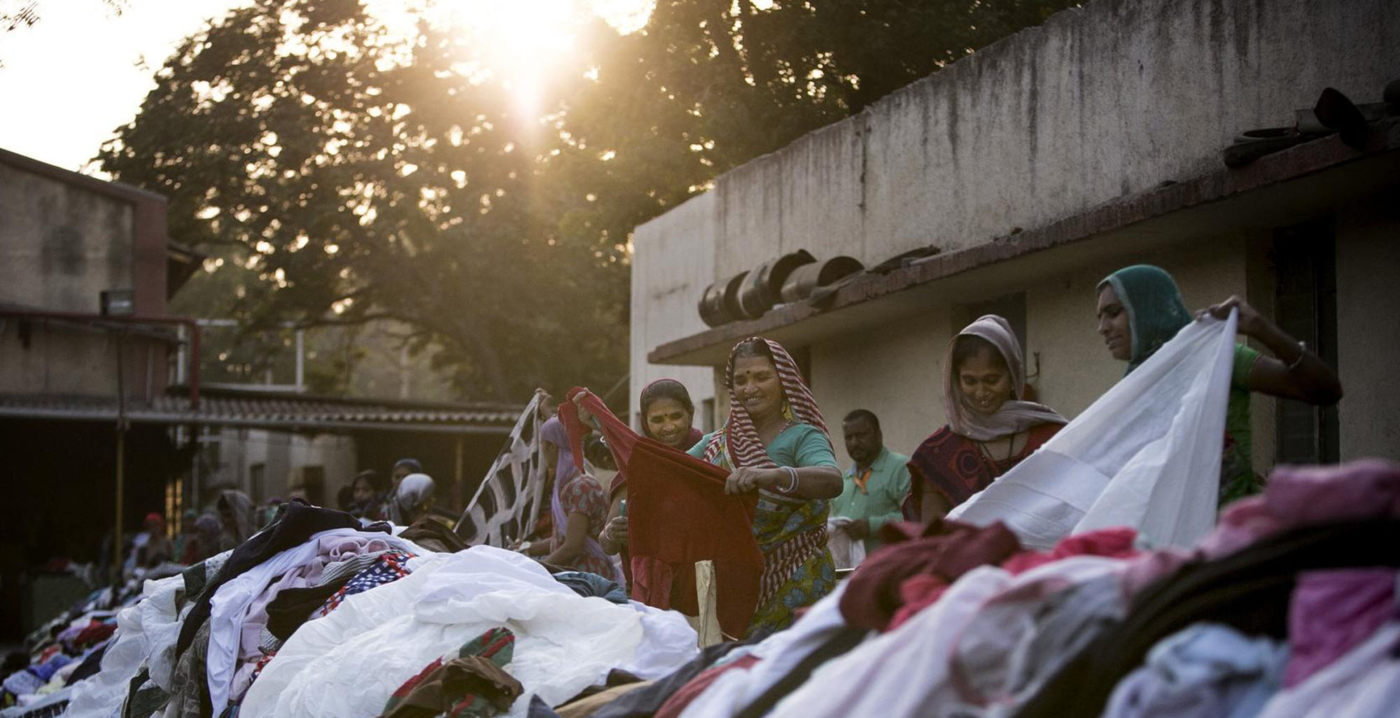 Women sort through clothes at the Canam International factory January 6, 2016 in Kutch, Gujarat. Dozens of warehouses in the Special Economic zone in Gujarat handle the sorting and recycling of tons and tons of donated clothes from the west. Allison Joyce for the Wall Street Journal
